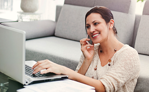 Woman talking on phone while on computer
