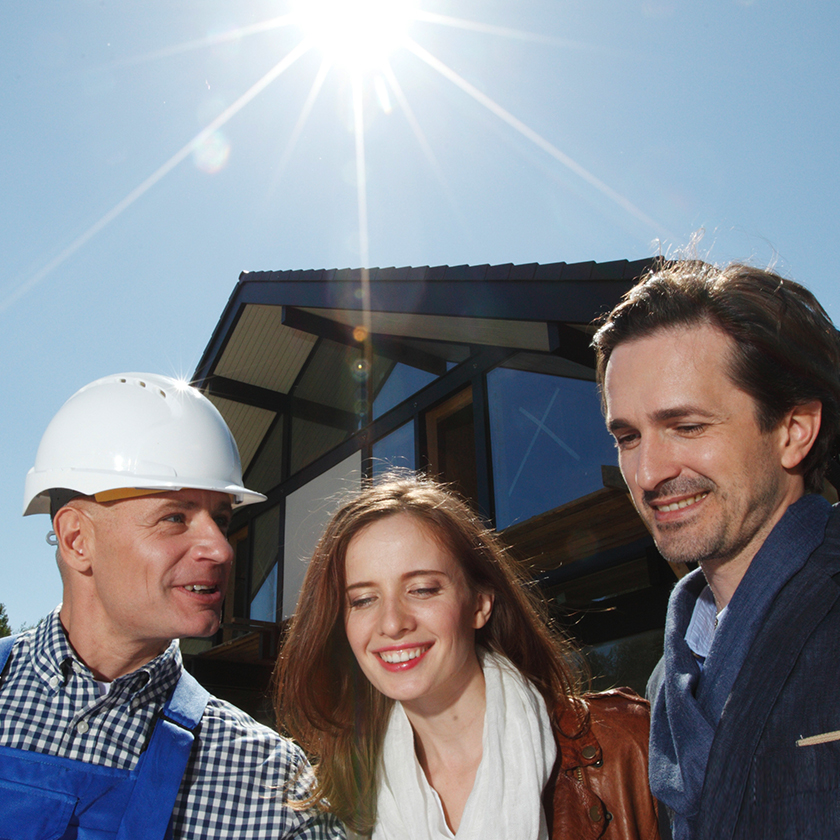 Couple with a contractor in front of home