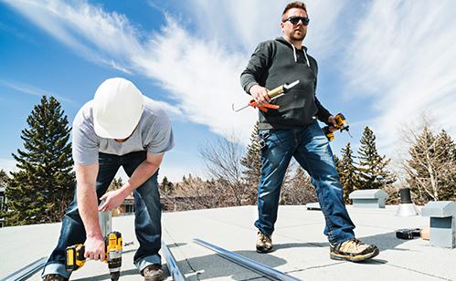 Two contractors installing solar panels
